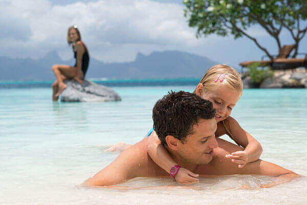 Family in a swimming pool in Tahiti