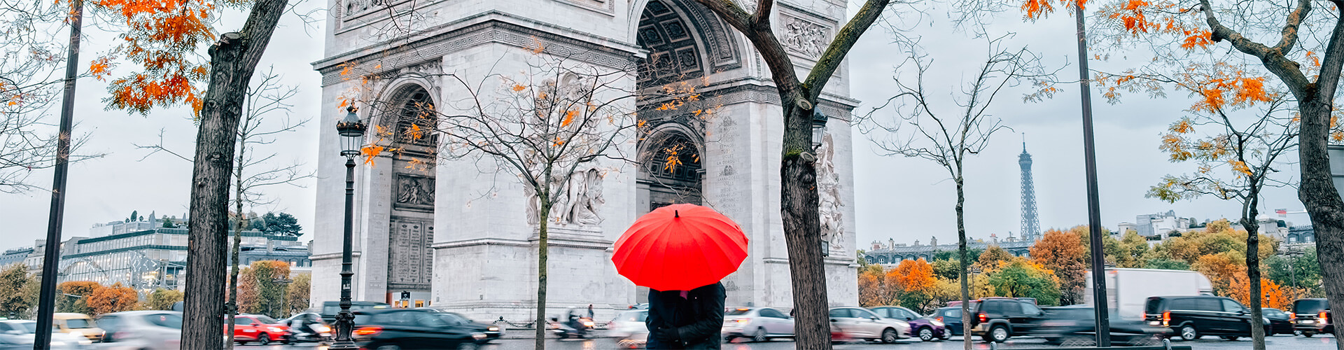 Couple in Paris under umbrella in front of the Arc de Triomphe