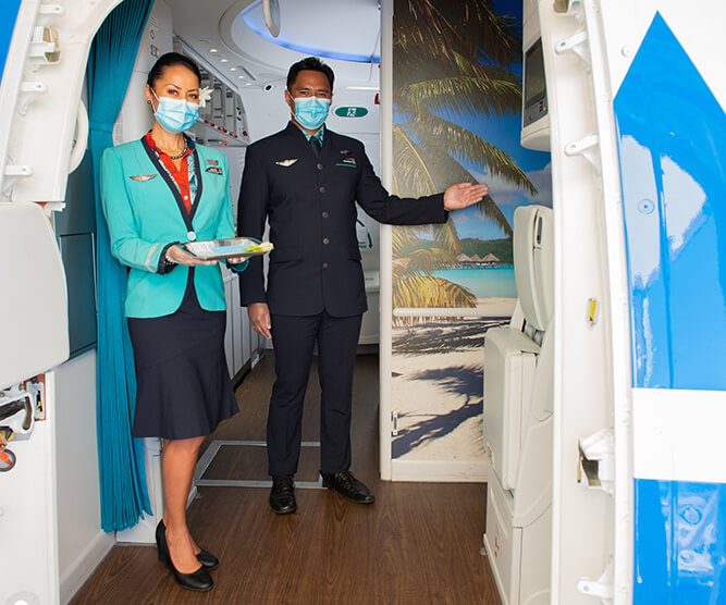 air tahiti nui crew welcoming passengers aboard at the entrance with mask