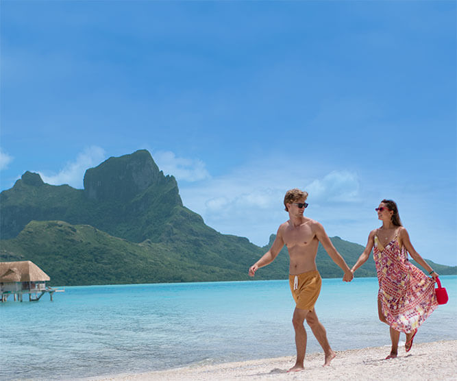 Couple walking on the beach in Bora Bora