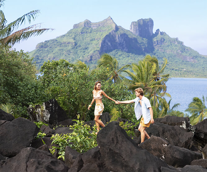 Couple hiking on lava rocks in Tahiti