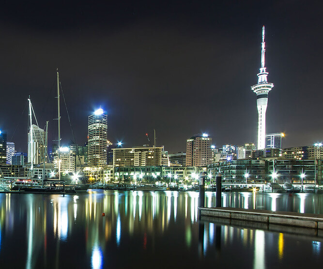 View of the city of Auckland by night with the sky tower