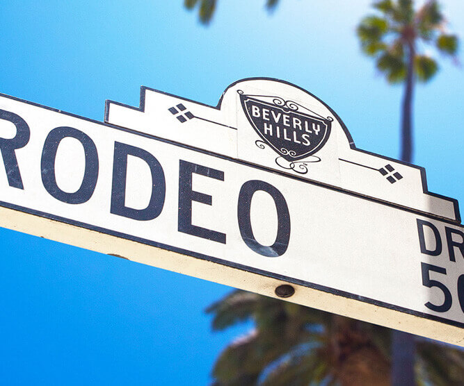 Photo of the street name of rodeo drive with blue sly behind
