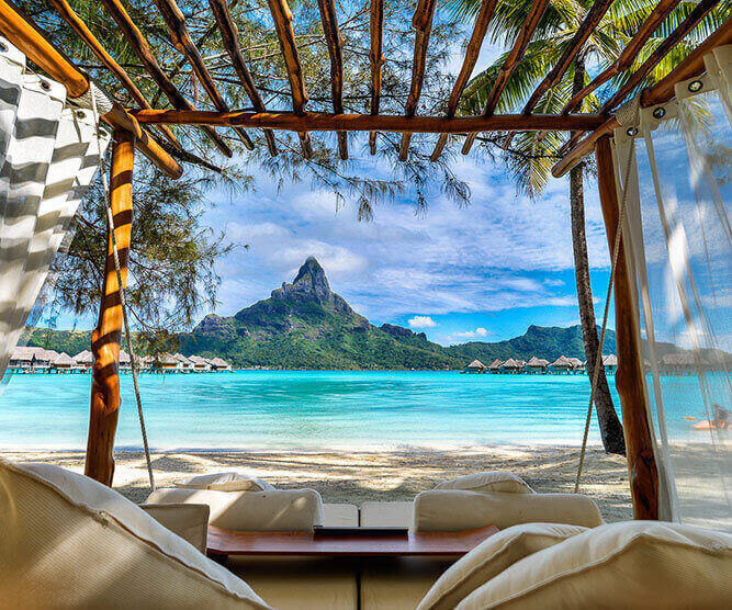 View of the mount Otemanu from a beach with a day bed in Bora Bora