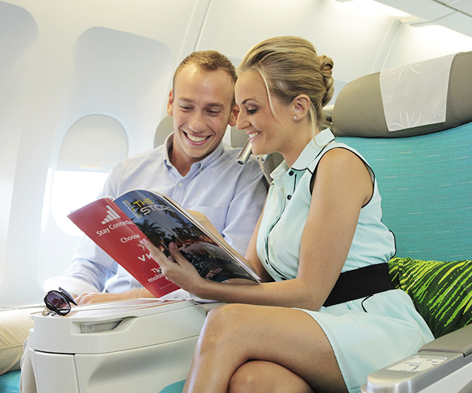 couple seating in air tahiti nui poerava business class and reading the duty free catalogue