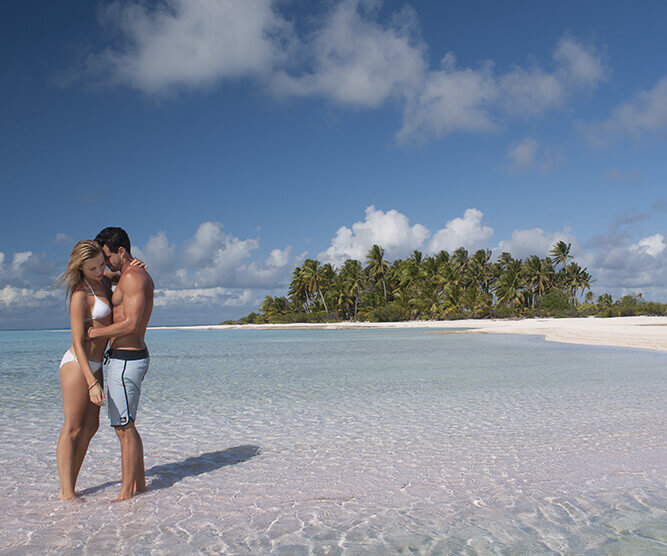 couple kissing on a beach with a motu island and the blue lagoon in background