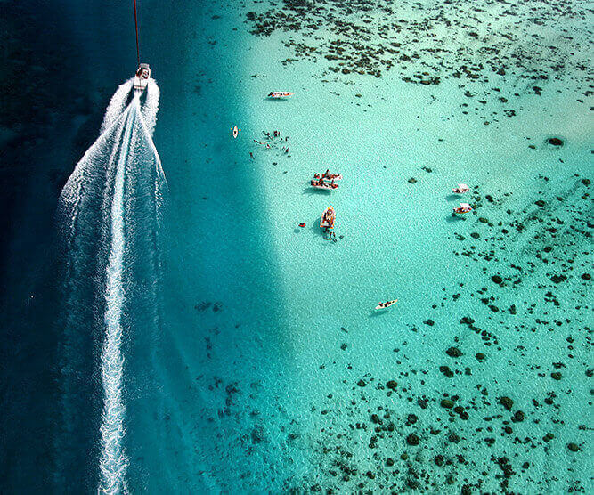 aeral view of a motor boat in the islands of tahiti ocean and people swimming in the turquoise lagoon
