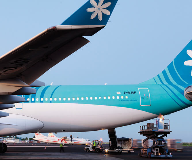 Photo of the air tahiti nui aircraft at the airport with a man going to the cargo on the tarmac of the airport