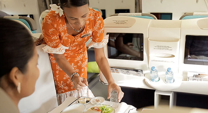 Air Tahiti Nui Flight attendant serving dinner to Business Class passenger