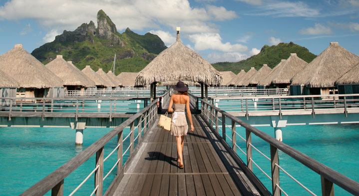 Woman walking on the pear of an hotel with overwater bungallow in Bora Bora