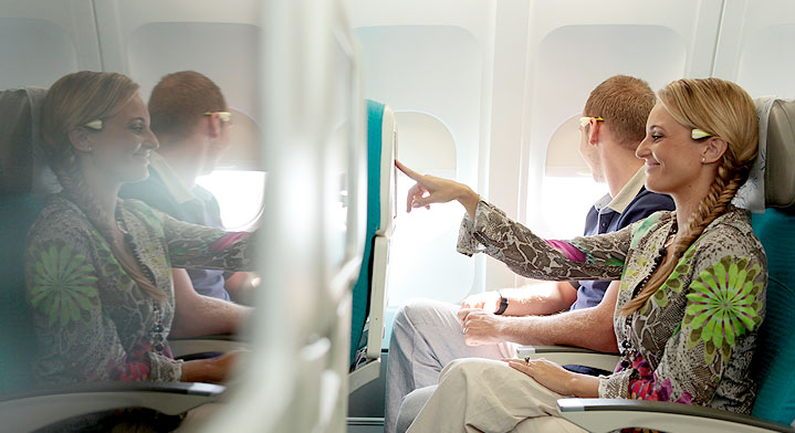 woman seating in Air Tahiti Nui economy class and enjoying a movie on her personal screen
