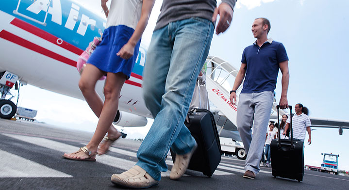 Photo of passengers walking on the Tahiti Faa'a tarmac with their carry on luggages