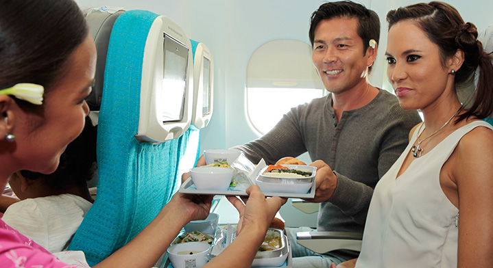 Flight attendant serving a meal to passenger in Air Tahiti Nui Economy Class