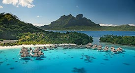 Tahiti - Woman floating in lagoon with overwater bungalows in the distance
