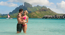 Couple standing in Tahiti lagoon embracing with boat and overwater bungalows in the distance