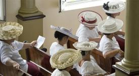 women on a church benches dressed in white and wearing Polynesian hats