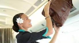 Air Tahiti Nui flight attendant that places a bag in the luggage racks