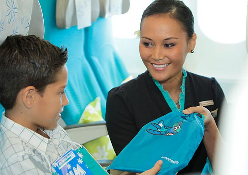 view of a flight attendant offering a kid kit to a young boy