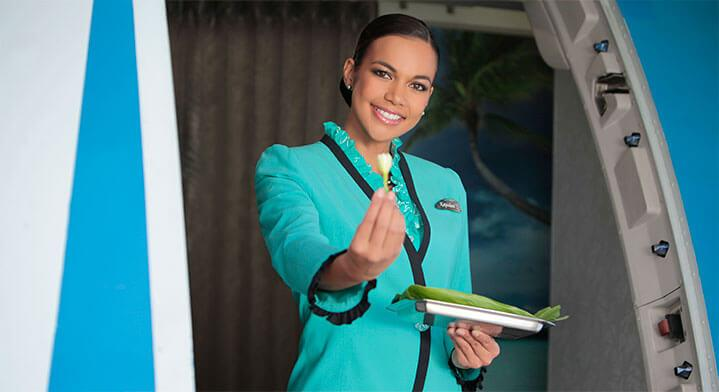 Air Tahiti Nui flight attendant - welcome aboard with tiara flower