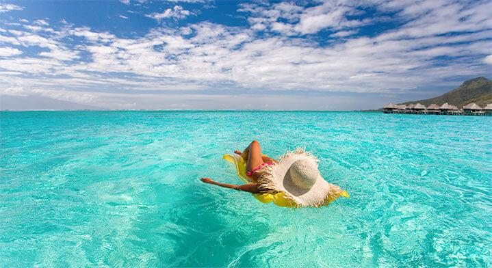 woman relaxing floating in lagoon in Tahiti