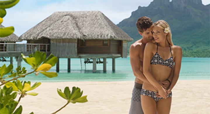 Early Booking - Bigger Savings Image Couple standing in front of lagoon and overwater bungalow