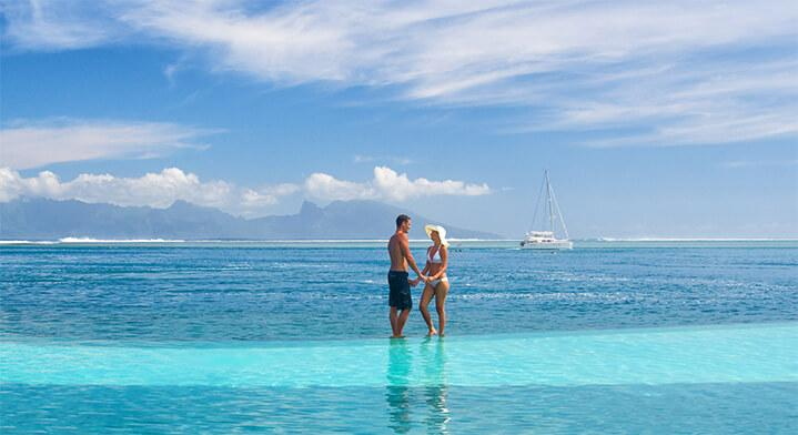 Couple standing near pool edge and lagoon in Tahiti