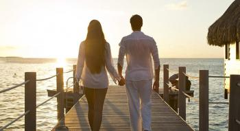 couple walking on a deck and watching a sunset