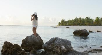 view of a woman posed on a rock taking a picture of the sea at tikehau