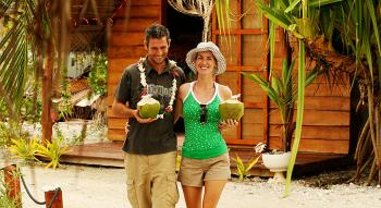 Couple drinking coconut water and walking on the beach