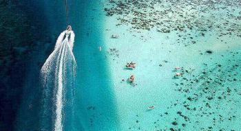 Aeral view of a motor boat in the islands of Tahiti ocean with the reel and lagoon