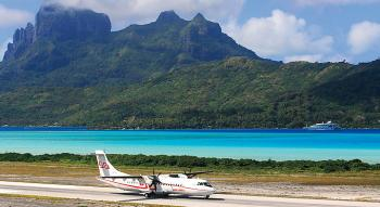 view an air tahiti aircraft on the tarmac and the lagoon and mountain on background