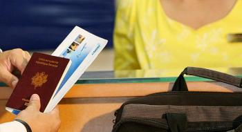 view of male hands tending a passport and an airline ticket to a hostess