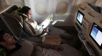 view of a passenger in a air tahiti nui business seat looking at a magazine with a night light beside a sleeping passenger