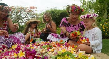Tahitian women with family working with native flowers