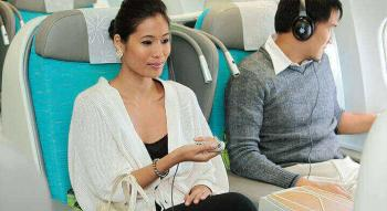 Couple seating in Air Tahiti Nui poerava Business Class listening music and watching a movie during their flight