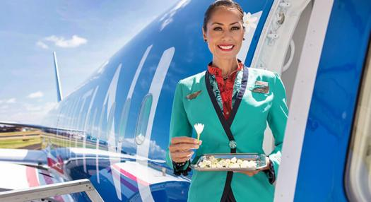 flight attendant welcoming air tahiti nui passenger with tiare flower