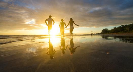 Photo of a family running by the beach at sunset
