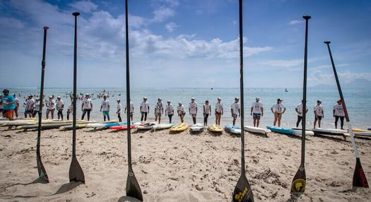 Photo of Waterman with their paddles on a beach of Tahiti