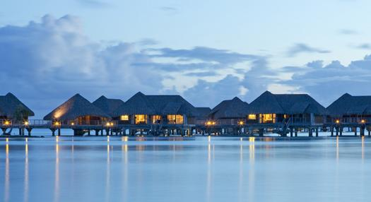 Photo of overwater bungalows at night