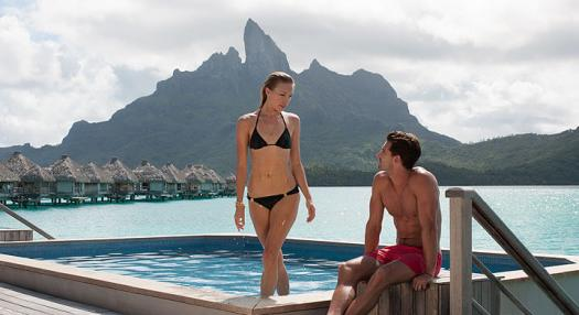 Woman standing up with a man seating in an hotel swimming pool with bora bora in background