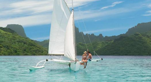 Couple on a traditional tahitian sail in bora bora