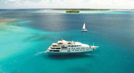 A view of a cruise ship and a sailing yatch on the lagoon of the islands of Tahiti