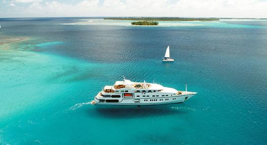 A view of a cruise ship and a sailing yatch on the lagoon of the Tuamotu's islands