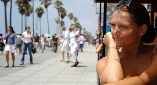 A woman sitting and watching people walking on Venice Beach in Los Angeles California