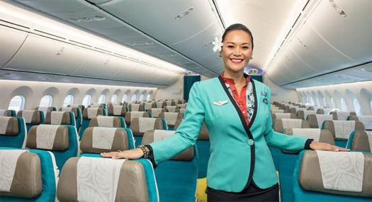 Air Tahiti Nui flight attendant smiling in the cabin of the new Dreamliner