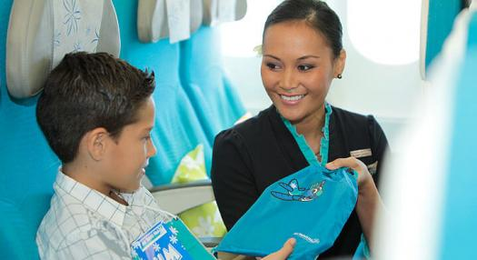 Photo of a flight attendant offering a kids kit to a young boy in the economy moana cabin