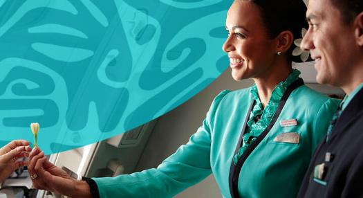Air tahiti nui flight attendant giving tiare flower to passengers