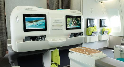 back of the seats of the Air Tahiti Nui Poerava Business Class Cabin with the entertainment screens