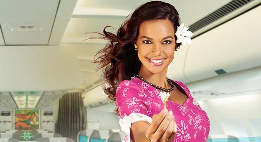 A filght attendant holding a Tiare flower in Air Tahiti Nui's Poerava Business Class