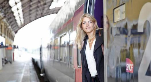 A woman standing in the TGV train in France and looking outside
